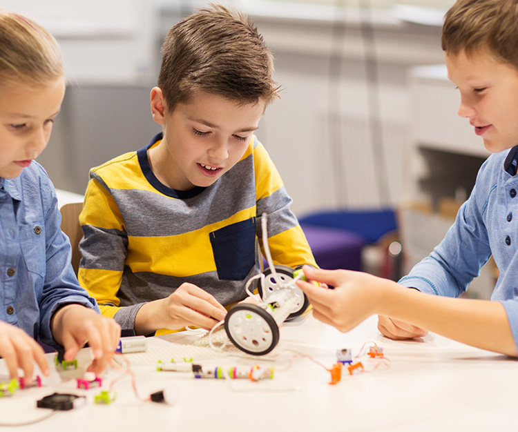 2 boys and a girl building a robotic vehicle on the table