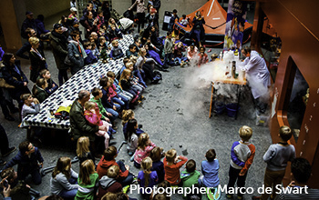 Mad scientist performing on a table with smoke, beakers, in front of children