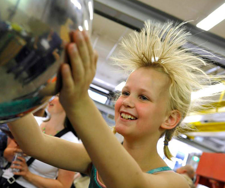 Blond girl touching van de graaff causing her hair to stand