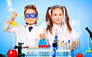 A boy wearing blue safety goggles and a girl wearing lab coats working with beakers in a lab