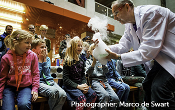 Mad scientist showing a beaker with smoke and bubble poring out to children while parents look on