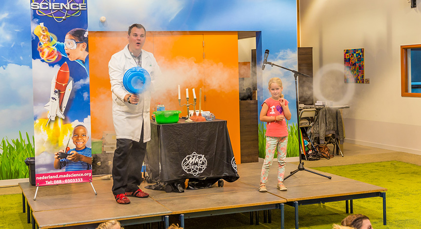 Mad scientist using smoke machine that is blowing rings while girl on stage looks on