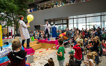 2 mad Scientist on stage in front of a group of kids one holding a yellow balloon