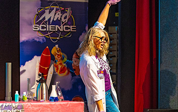 A mad scientist with her hand in the air wearing purple gloves in front of red table with science equipment on it.